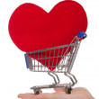 Heart symbol in shopping trolley on the palm - Stock Photo