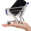 Smartphone in shopping trolley on the palm — Stock Photo