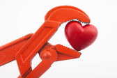 Orange wrench pressing a red heart — Stock Photo
