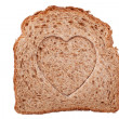 Heart shaped hole in a slice of bread — Stock Photo