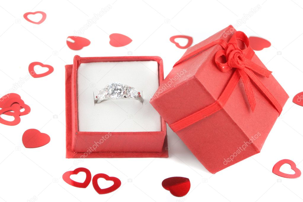 Red gift box holds a diamond engagement ring with valentine heart confetti — Photo #7974744