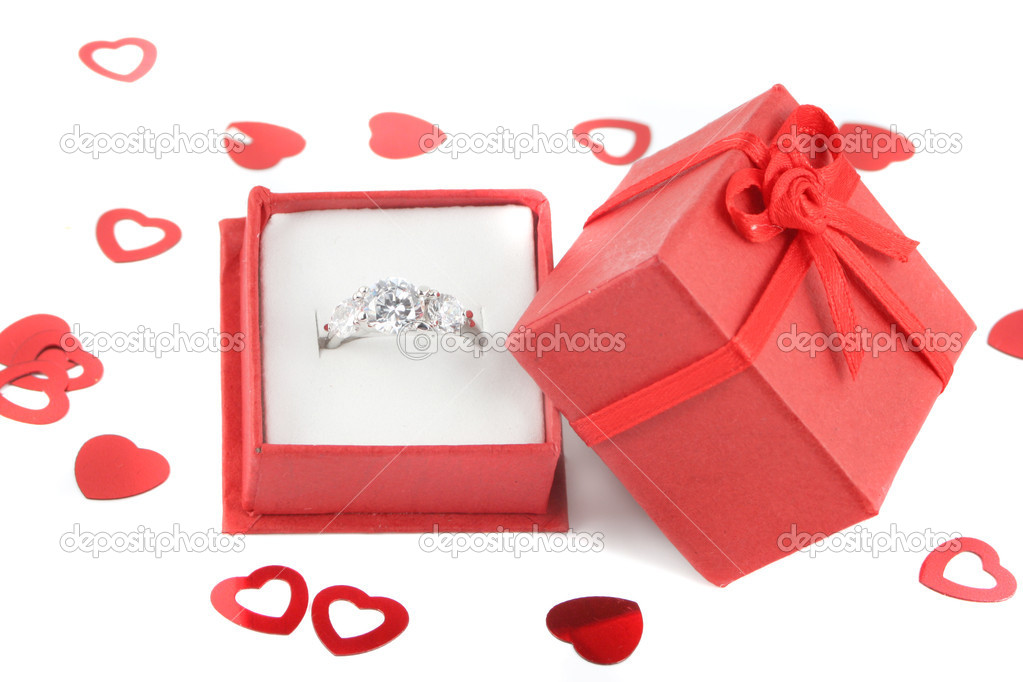 Red gift box holds a diamond engagement ring with valentine heart confetti — Stock fotografie #7974744