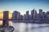 Luzes de new york city e a ponte de brooklyn ao pôr do sol — Foto Stock