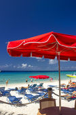Red Beach Umbrellas and turquoise Waters of Caribbean — Stock Photo