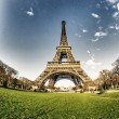 Curves of the Eiffel Tower under blue sky at shiny Winter mornin - Stock Photo