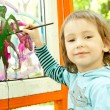 Cute little girl is drawing on the glass — Stock Photo