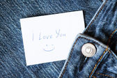 """Blue jeans with with hand printed card """"i love you"""" — Stock Photo"""