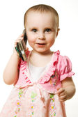 Little girl talking on the phone in a pink dress — Stock Photo