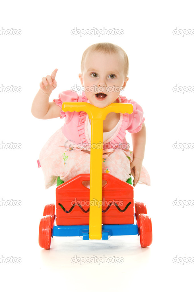 Baby sitting on a trolley on a white background. — Stock Photo #10463339