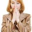 Praying woman in business suit with gold on a white background. — Stock Photo #8365976