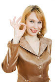 Beautiful business woman in a gold suit with a gesture ok shows a white — Stock Photo