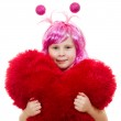 A girl with pink hair and a pink dress cuddle pillow in the form of the hea — Stock Photo #8789701