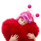 A girl with pink hair and a pink dress cuddle pillow in the form of the hea — Stock Photo