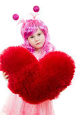 A girl with pink hair and a pink dress holding a pillow in the shape of hea — Stock Photo