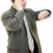Businessman looking at his watch and talking on the phone on a white backgr — Stock Photo #8790715