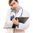 Male doctor talking on the phone and writing on the document plate on a whi — Stok fotoğraf