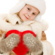 Girl in warm clothing holding the heart in his hands on a white background. — Stock Photo