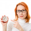 A beautiful girl with red hair wearing glasses points his finger at the clock on a white background. — Stock Photo #9688833