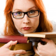 Beautiful red-haired girl in glasses reads book. — Stock Photo #9689579