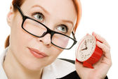 Businesswoman wearing glasses listening clock . — Stock Photo