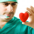 Doctor with a heart and  syringe in his hand — Stock Photo
