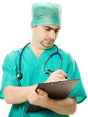 Male surgeon writes on the tablet — Stockfoto