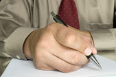 Hand with pen writing on the white paper — Stock Photo