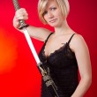 Young beautiful blonde girl holding sword — Stock Photo