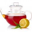 Teapot with black tea, green leaves and lemon slices isolated on — Stock Photo