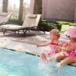 Two little sisters playing in swimming pool — Foto de Stock