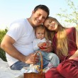 Happy young family with child outdoors — Stock Photo