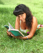 Young smiling woman reading in summer park — Stock Photo