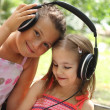 Two sisters listen to the music outdoor — Stock Photo