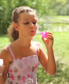 Portrait of the pretty little girl blowing bubbles — Stock Photo