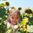 Stock Photo: Cute child with sunflower in summer field