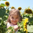 Cute child with sunflower in summer field — Stock Photo