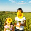 Two cute litle girls hiding behind sunflowers - Stock Photo