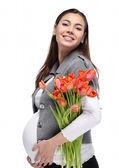 Gelukkig zwangere vrouw met tulpen — Stockfoto