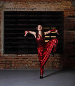 Young brunette woman in red dancing — Stock Photo
