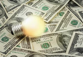 Lamp on dollars background — Stock Photo