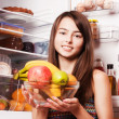 Stock Photo: Smile girl with fruits on the kitchen