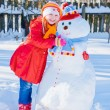 Stock Photo: Snowman and young girl