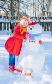 Snowman and young girl — Stock Photo