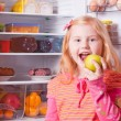 Girl with food on background refrigerator — Stock Photo
