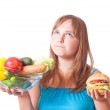 Girl with vegetables and hamburger — Stock Photo