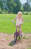 Little girl on bicycle outdoors — Stock Photo
