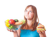 Girl with vegetables and hamburger — Stock fotografie