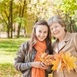 Girl with grandmother in autumn park — Stock Photo