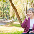 Elderly women with phone in autumn park - Stock Photo