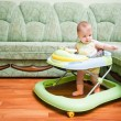 Baby in the baby walker - Stock Photo